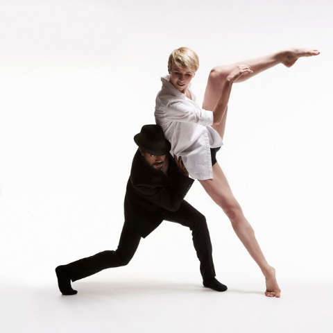 Two dancers on a white backdrop.