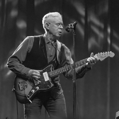 Bruce Cockburn in black and white playing electric guitar.