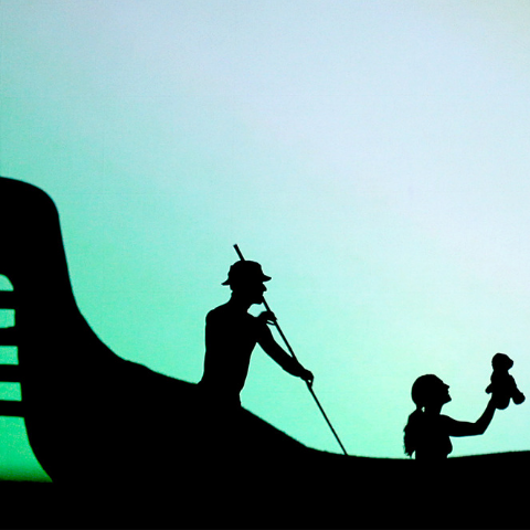 A shadow of a man rowing an Indigenous style canoe with a girl on board holding a teddy bear.