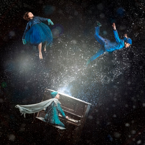 Three people floating in the air dressed in blue with one man playing a piano.