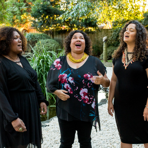Four women singing outside.