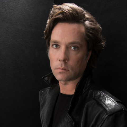 Rufus Wainwright posing in a black leather jacket.