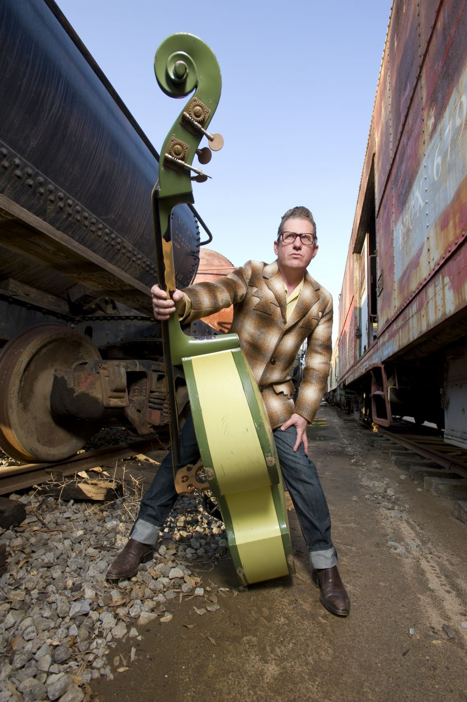 Lee Rocker in between two trains with his bass guitar.