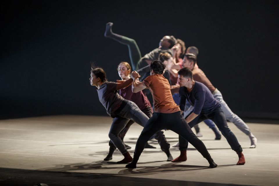 Multiple dancers on stage leaning forward.