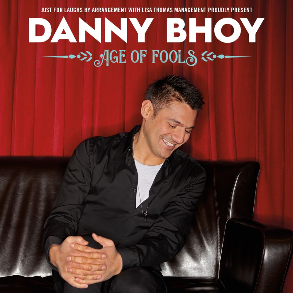 Danny Bhoy sitting on a leather couch laughing