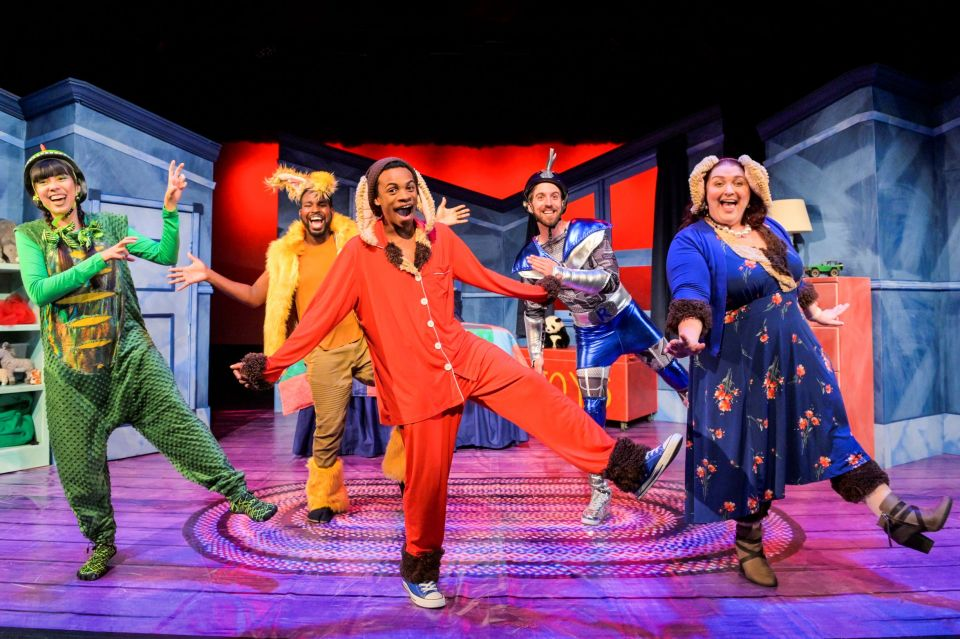 Five people dancing on stage dressed as characters from the book in colourful costumes