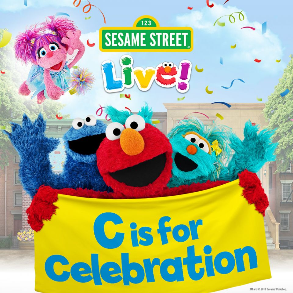 Sesame Street Live! characters dancing on stage.