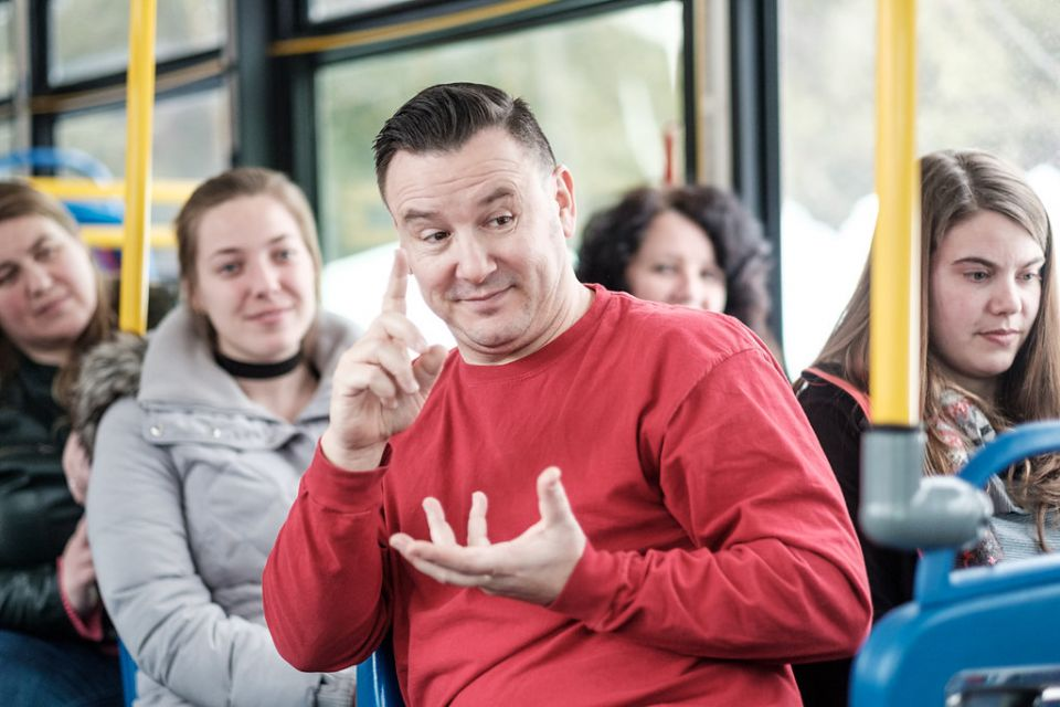 actor in a red shirt sits on a public transit bus